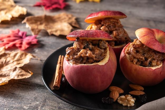 Pommes farcies cuites au four avec des noix sur table en bois