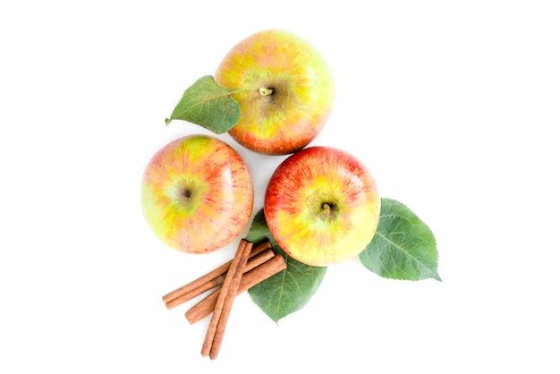 Pommes avec des feuilles et des bâtons de cannelle isolés sur fond blanc.
