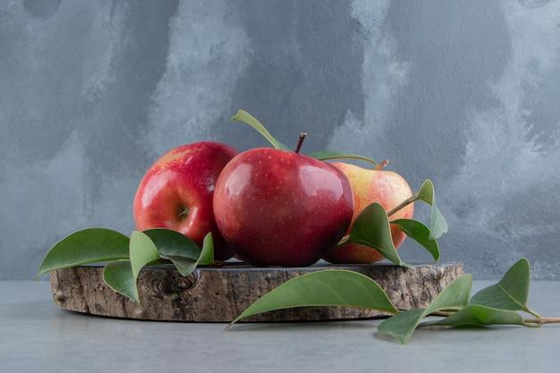 Pommes et feuilles regroupées sur une planche de bois sur marbre.