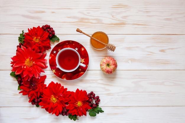 Pommes, fleurs de dahlia rouge, baies rouges et miel avec espace de copie