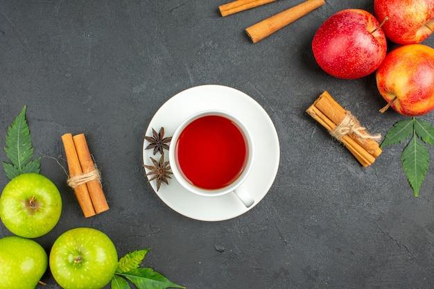 Pommes fraîches biologiques naturelles avec des feuilles vertes, des citrons verts à la cannelle et une tasse de thé noir sur fond noir