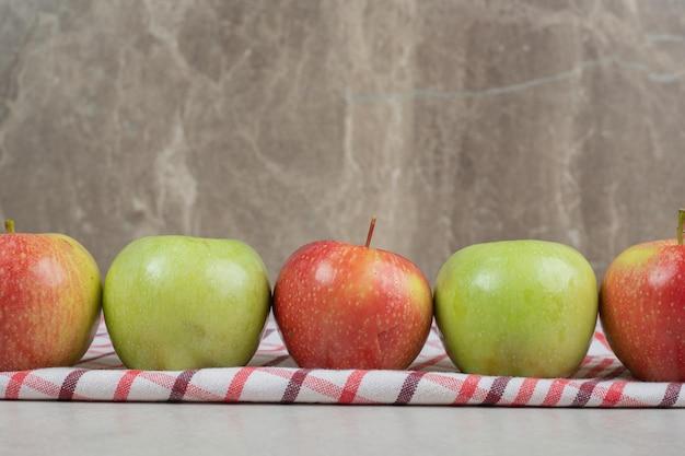 Pommes fraîches colorées sur nappe à rayures.