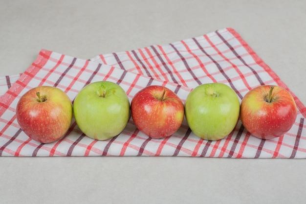 Pommes fraîches colorées sur nappe à rayures