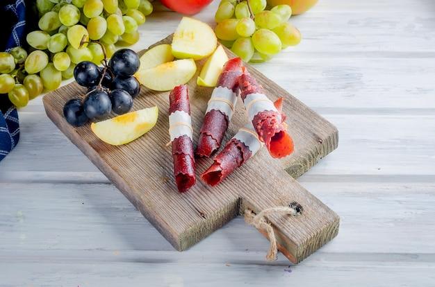 Pommes fraîches cueillies, raisins et pastille de fruits sur une surface sombre