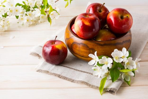 Pommes fraîches dans le bol en bois et fleur de pommier