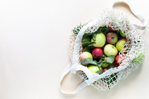 Pommes fraîches dans un filet de sac à provisions. zéro déchet, pas de concept plastique. une alimentation saine et détox. récolte d'automne. mise à plat, vue de dessus.