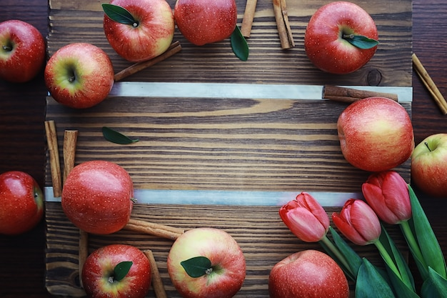 Pommes fraîches sur une planche de bois. récolte de pommes rouges. fruits et cannelle sur la table.
