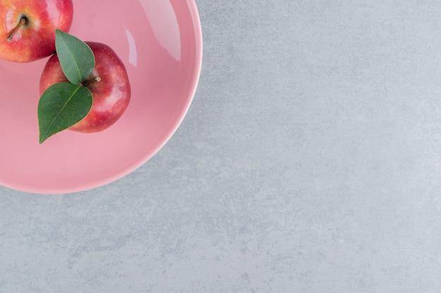 Pommes fraîches sur un plateau rose sur marbre.