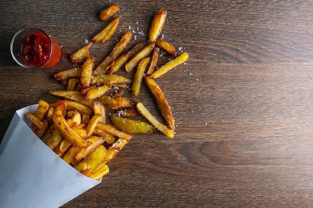 Pommes frites dans un sac en papier avec des sauces sur un fond en bois