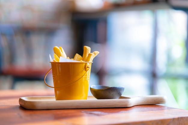 Pommes frites et ketchup sur planche de bois