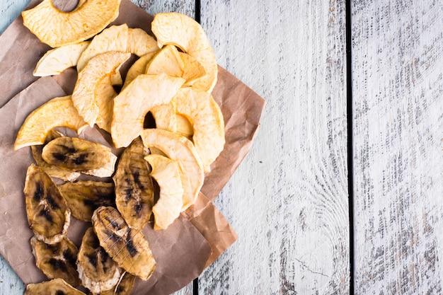 Pommes de fruits et chips de banane sur fond de table en bois.