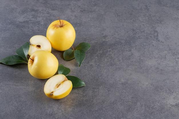 Pommes jaunes entières et tranchées placées sur une table en pierre.
