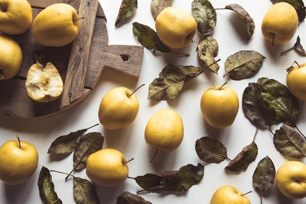 Pommes jaunes sur une planche en tranches dans un style vintage. feuilles, nourriture, nourriture saine, végétalienne, produit de la ferme.