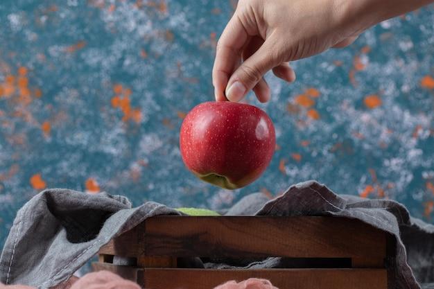 Pommes juteuses sur boîte en bois rustique.