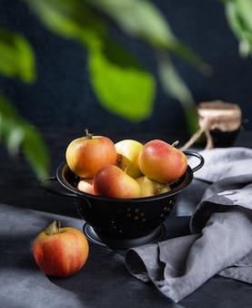 Pommes juteuses dans un bol noir avec une serviette en lin et un pot de confiture sur un fond sombre. vue de face et image sombre