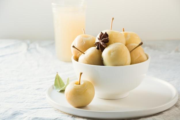 Pommes marinées dans un bol et pomme sidr sur la table en pierre blanche.