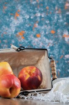 Pommes sur mini panier métallique sur bleu.