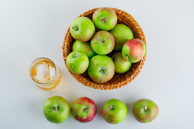 Pommes mûres avec du jus dans un panier en osier sur blanc.