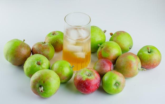Pommes mûres avec du jus de glace sur blanc, vue grand angle.