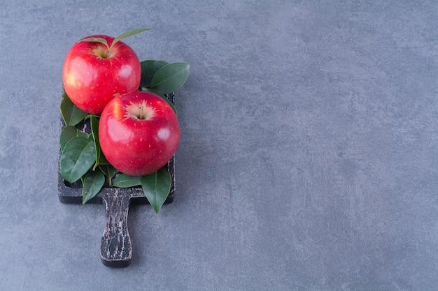 Pommes mûres avec des feuilles à bord sur la surface sombre