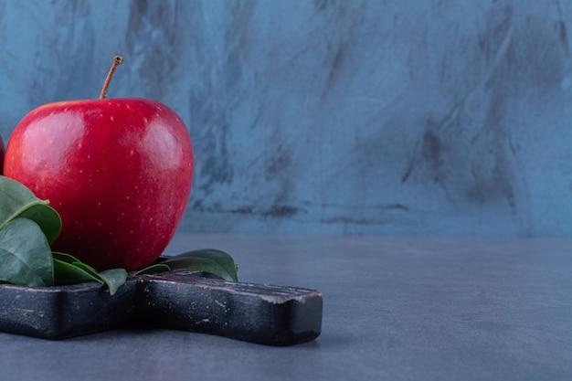 Pommes mûres avec des feuilles à bord sur une table en marbre.