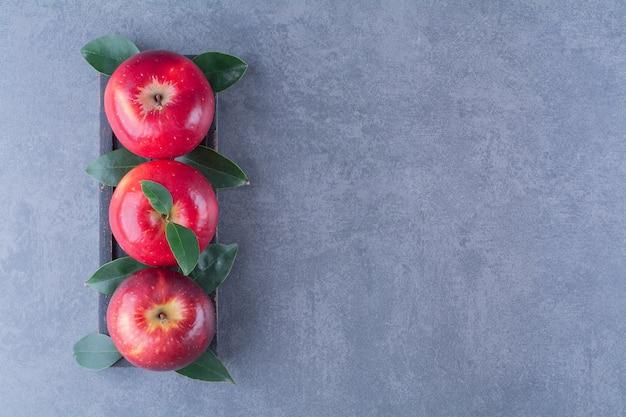 Pommes mûres et fraîches avec des feuilles sur un plateau en bois sur la surface sombre