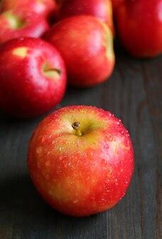 Pommes mûres fraîches avec des gouttelettes d'eau isolés sur une table en bois noir