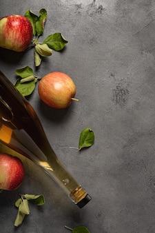 Pommes mûres fraîches et vinaigre de cidre de pomme. cidre de pomme dans une bouteille en verre et pommes fraîches. vue de dessus. . copiez l'espace de votre texte.