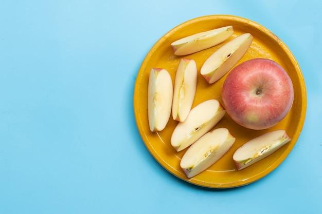 Pommes mûres sur plaque jaune sur fond bleu.