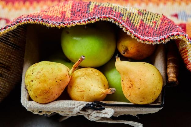 Pommes mûres et poires dans le panier