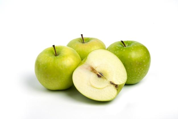 Pommes mûres vertes sur fond blanc.