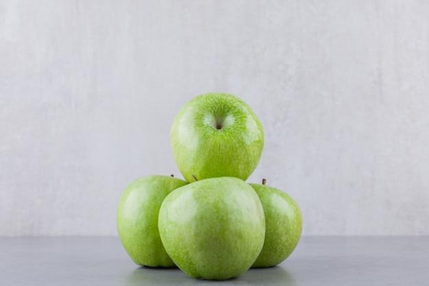 Pommes mûres vertes fraîches placées sur une table en pierre.