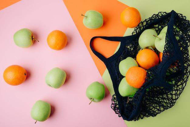 Pommes et oranges dans un sac à cordes bleu