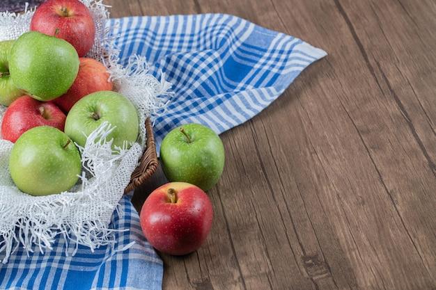 Pommes sur panier en bois sur toile de jute blanche.