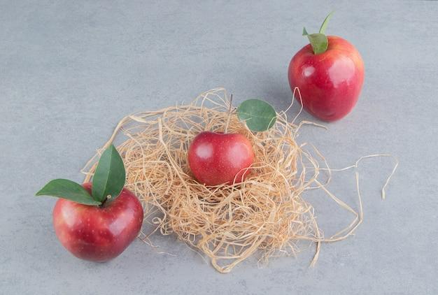 Des pommes et un petit tas de paille sur du marbre.