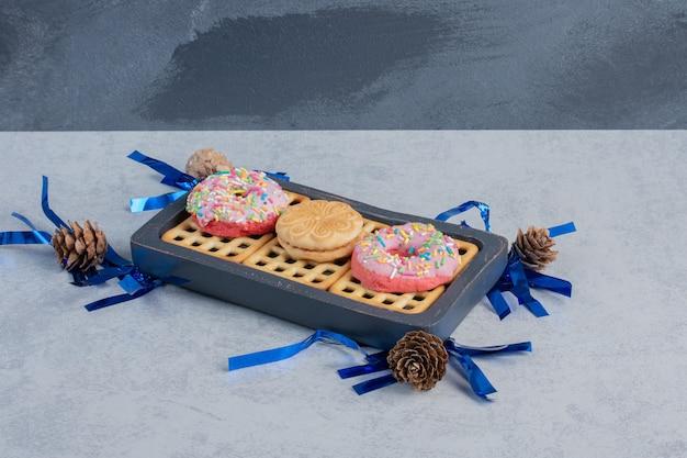 Pommes de pin autour de beignets, biscuits et une marmelade sur un petit plateau sur une surface en marbre