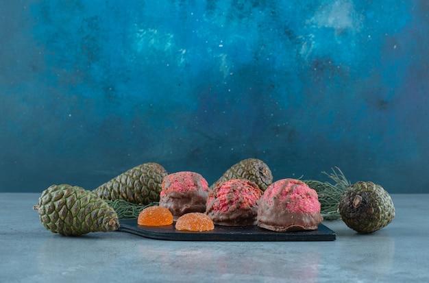Pommes de pin autour d'une planche avec des desserts sur marbre.