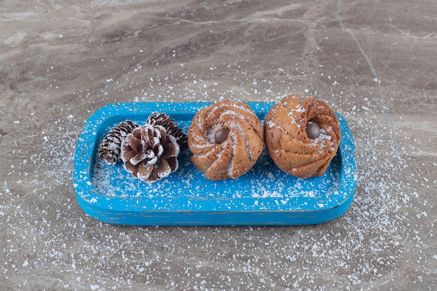 Pommes de pin et biscuits sur un plateau bleu sur une surface en marbre