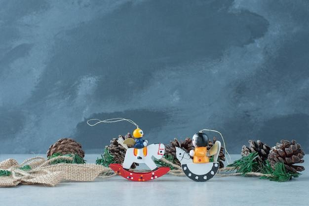 Pommes de pin avec de petits jouets de fête de noël sur fond de marbre. photo de haute qualité