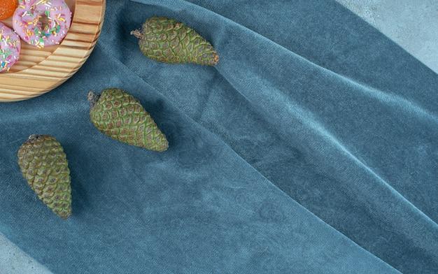 Des pommes de pin et un plateau de beignets sur textile.