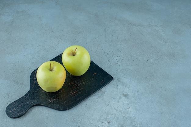Pommes sur une planche à découper, sur le fond de marbre. photo de haute qualité