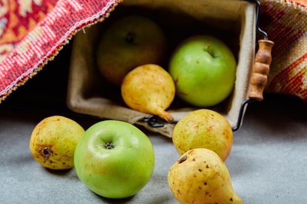 Pommes et poires mûres dans le panier et sur une surface blanche.