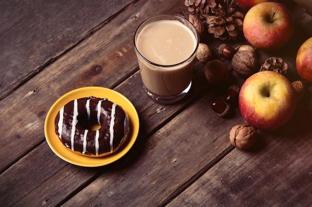 Pommes, pommes de pin, tasse de café, beignet et noix