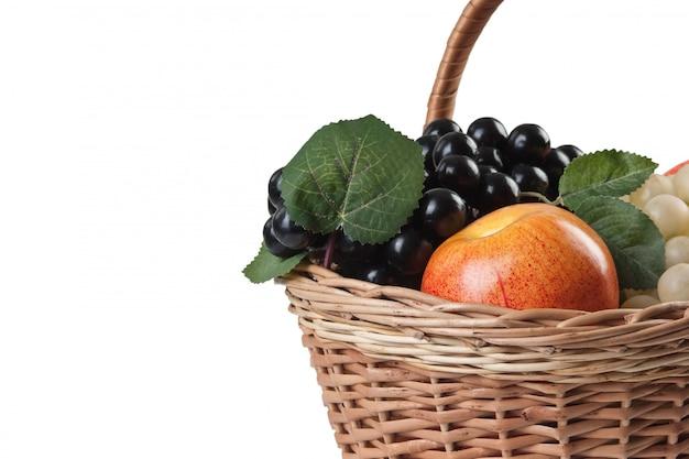 Pommes et raisins dans un panier isolé sur fond blanc