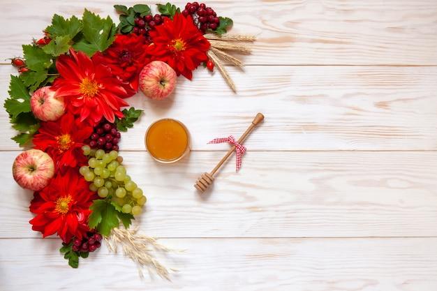 Pommes, raisins, fleurs de dahlia rouge, baies rouges et miel avec espace de copie