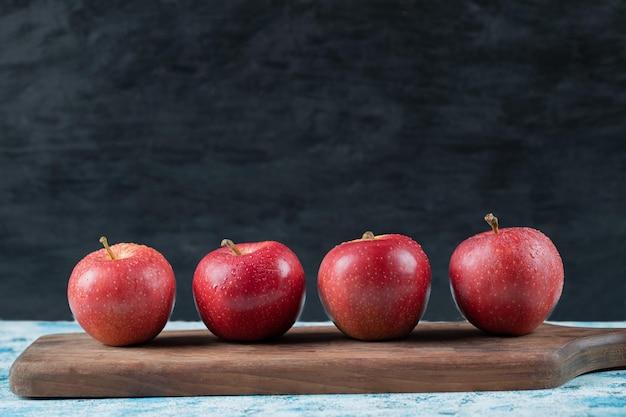Pommes sur rangée sur planche de bois étroite.