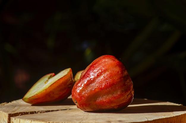 Pommes roses (syzygium jambos) sur table en bois avec fond sombre