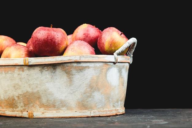 Pommes rouges biologiques fraîches dans un panier sur fond noir
