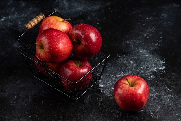 Pommes rouges biologiques mûres dans un panier en métal sur une surface noire. .