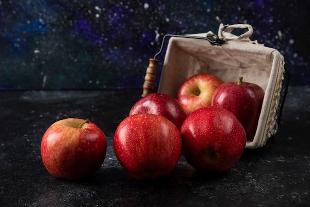 Pommes rouges biologiques mûres hors du panier sur une surface noire. .
